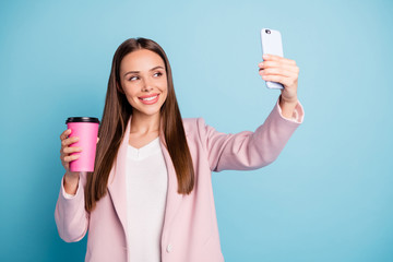 Portrait of cute cheerful lady using her cellphone making selfie holding mug with hot beverage wearing pink coat isolated over blue color background