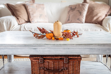 autumn table decoration in a cozy living room, wicker basket, pillows, leaves pumpkin, butternut...