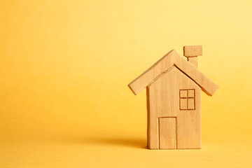 Homemade wooden house on a yellow background