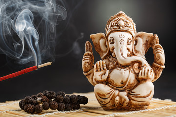 Ganesha on a black background. Statue and rosary with red smoldering incense stick