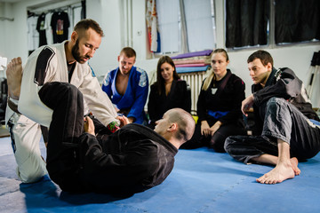 Brazilian Jiu jitsu bjj black belt teaching class or private lessons to his students at the academy martial arts ground fight