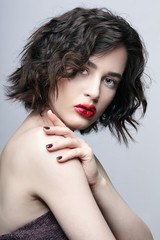 Brunette girl with unusual alyapy red female face makeup