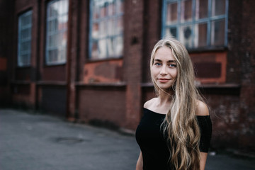 Young blond woman with long hair in a black dress near a brick red wall. Stylish girl in the city.