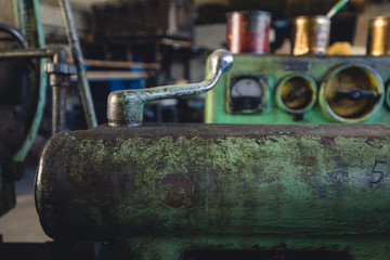 Rusty mechanisms and tools in the shop of an old abandoned factory.