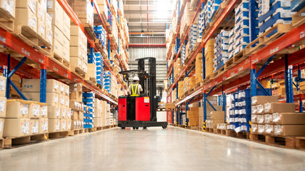 Worker in forklift-truck loading packed goods in huge distribution warehouse with high shelves. Wall mural