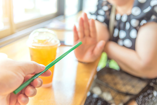 Close up hand holding straw and say no for plastic drinking straw. Concept related to banned plastic drinking straws, environmental concerns. x