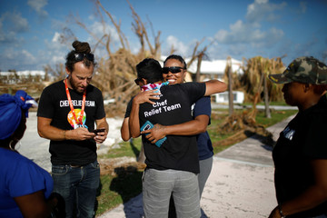 Volunteers of the NGO World Central Kitchen embrace before a food distribution operation, after Hurricane Dorian hit the Abaco Islands in Marsh Harbour