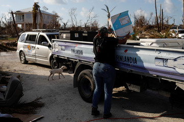A volunteer of the NGO World Central Kitchen loads food for distribution on a truck after Hurricane Dorian hit the Abaco Islands in Marsh Harbour