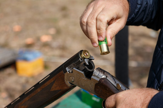 Charging a hunting rifle. Male hunter charges a double-barreled shotgun rounds. Male with a gun, rifle