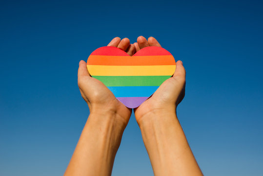 Woman holds in hands a heart in the colors of the rainbow. Young beautiful girl. LGBT history month. Pride Month. Lesbian Gay Bisexual Transgender. LGBT flag. Love, human rights, tolerance. LGBTQ+