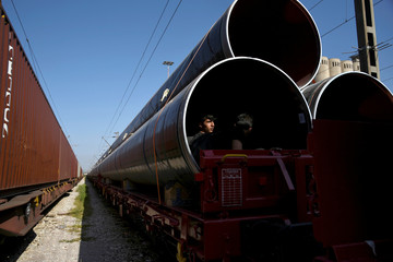 Migrants hide in a tube carried by a freight train platform, in an effort to reach and cross the Greek-North Macedonian border without documents, in Thessaloniki