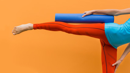 Creative fashion fitness image of sporty girl with yoga mat over bright  background