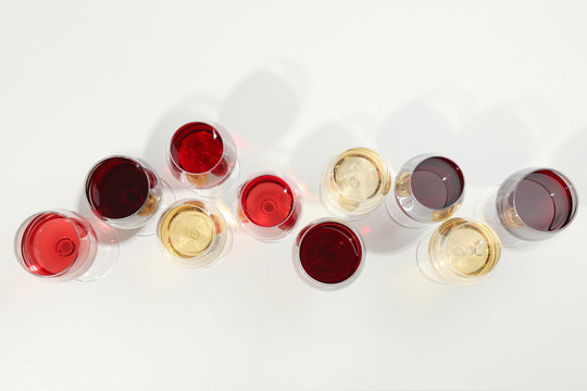 Flat lay composition. Glasses with different wine on white background, top view