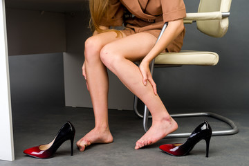 Woman suffering from leg pain in office.
