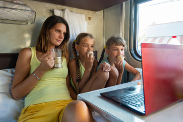 Mom drinks tea, children eat ice cream on a train, look at a laptop together