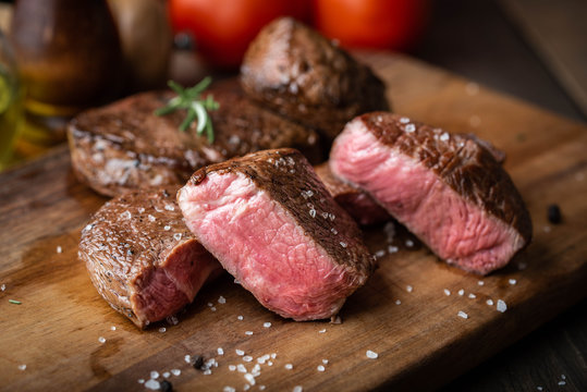 rare grilled tenderloin beef steak on cutting board with vegetables