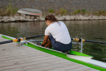 Girl athlete engaged in canoeing on a water channel. The concept of health and sport.Woman Single sculls rower. female  engaged in rowing on the river
