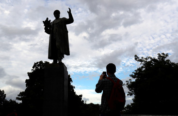 A man takes a picture of the monument of Soviet World War II commander Ivan Stepanovic Konev in Prague