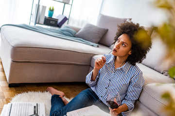 Smiling young African female entrepreneur sitting at a floor in her home using digital tablet and drink wine. Relaxing work at home. African female working on tablet computer at home