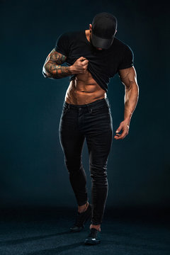 Strong and fit man bodybuilder shows abdominal muscles under a t-shirt. Sporty muscular guy athlete. Sport and fitness concept. Men's fashion.