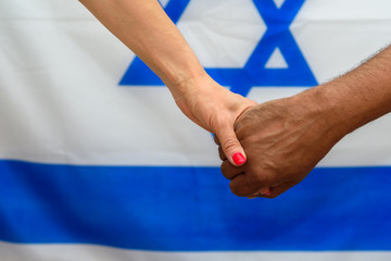 Woman and man holding hands on Israel flag background.