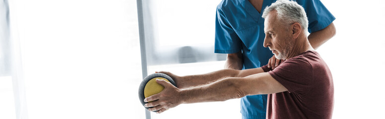 panoramic shot of middle aged man exercising with ball near doctor