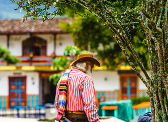 Man wearing a sombrero and folded poncho over the shoulder in colonial village of Jardin, Colombia