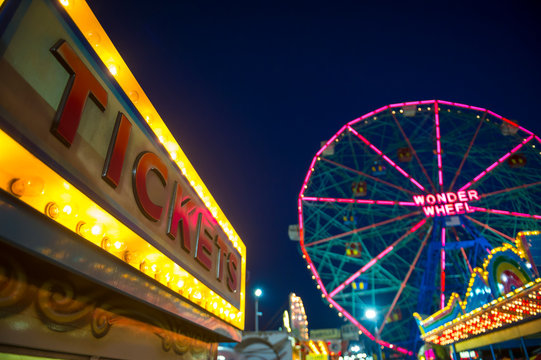 NEW YORK CITY - AUGUST 20, 2017: The bright lights of Coney Island glow from the boardwalk in front of a dark Brooklyn sky.