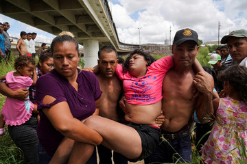 Breni, a Honduran girl who is seeking asylum in the U.S., is carried from the Rio Grande in distress, where she had been bathing in Matamoros, Mexico