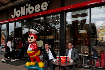 Ernesto Tanmantiong, President and CEO of Philippine national champion Jollibee Foods Corp, and CFO Ysmael Baysa, pose for a picture outside a Jollibee branch in Pasig City