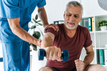 selective focus of mature man working out with dumbbell near doctor