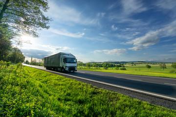 Fotobehang - White truck driving on the asphalt road in a green rural landscape