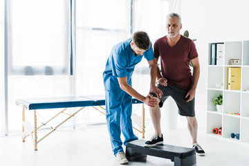 handsome doctor touching knee of mature patient on step platform Wall mural