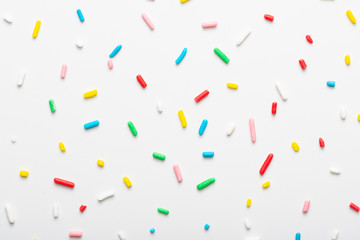 flat lay of colorful sprinkles over white background, festive decoration