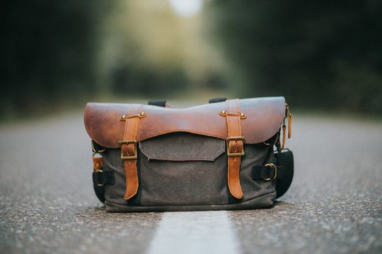 Closeup shot of a leather hiking bag on a road