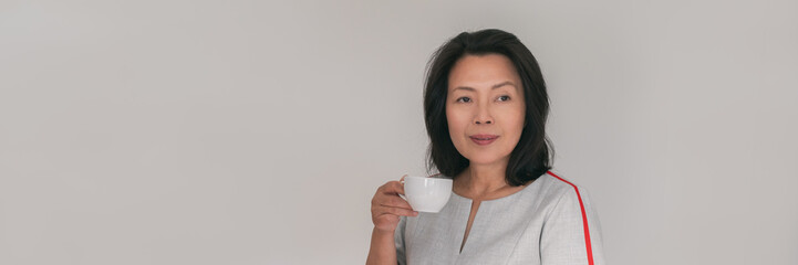 Mature Asian woman drinking coffee cup relaxing at cafe or office taking a break from work panoramic banner business people lifestyle. Lady in her 50s.