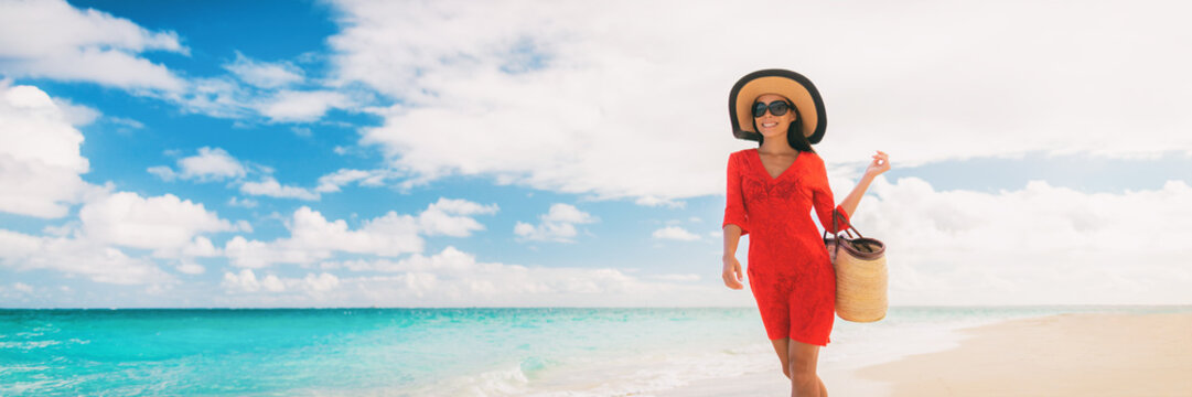 Luxury beach vacation elegant lady walking on beach stroll with beachwear sun hat and straw tote bag wearing red cover-up dress panoramic banner.