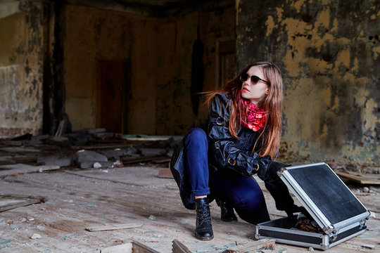 Girl in a black cloak with a diplomat in a ruined room. A spy in a secret meeting. Unusual photo shoot