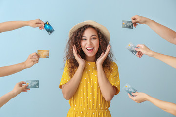 Obraz Young African-American woman and hands with credit cards on color background - fototapety do salonu