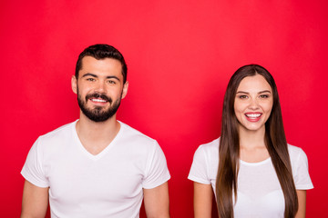 Photo of charming cute nice handsome beautiful couple looking at you while isolated with red backgroung with white t-shirts Fototapete