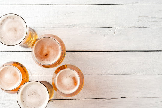 Set of beer glasses on vintage wooden background with copyspace. Top view