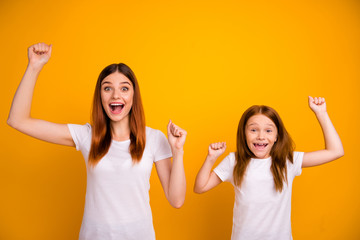 Portrait of crazy lovely people with long haircut raising fists screaming wow omg wearing white t-shirt isolated over yellow background