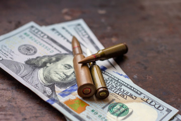 Diverse weapon bullets on American dollars background. Military industry, war, global arms trade and crime concept