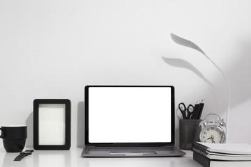 Laptop,books,Pencil,lamp light clock,cup coffee on white table copy space for your text .work desk arrangement concept