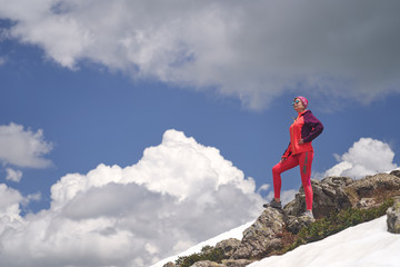 Portrait of hiking woman in red at the beautiful mountains background.