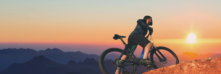 Cyclist in shorts and jersey on a modern carbon hardtail bike with an air suspension fork rides off-road on the orange-red hills at sunset evening in summer	 Fototapete