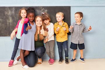 Kinder und Lehrerin mit Daumen nach oben