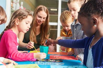 Kinder und Lehrerin malen mit Wasserfarbe