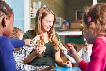 Betreuerin und Kinder spielen mit Knete