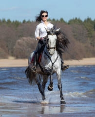 Fototapete - Horse woman and Spanish horse speed running into sea with splashes